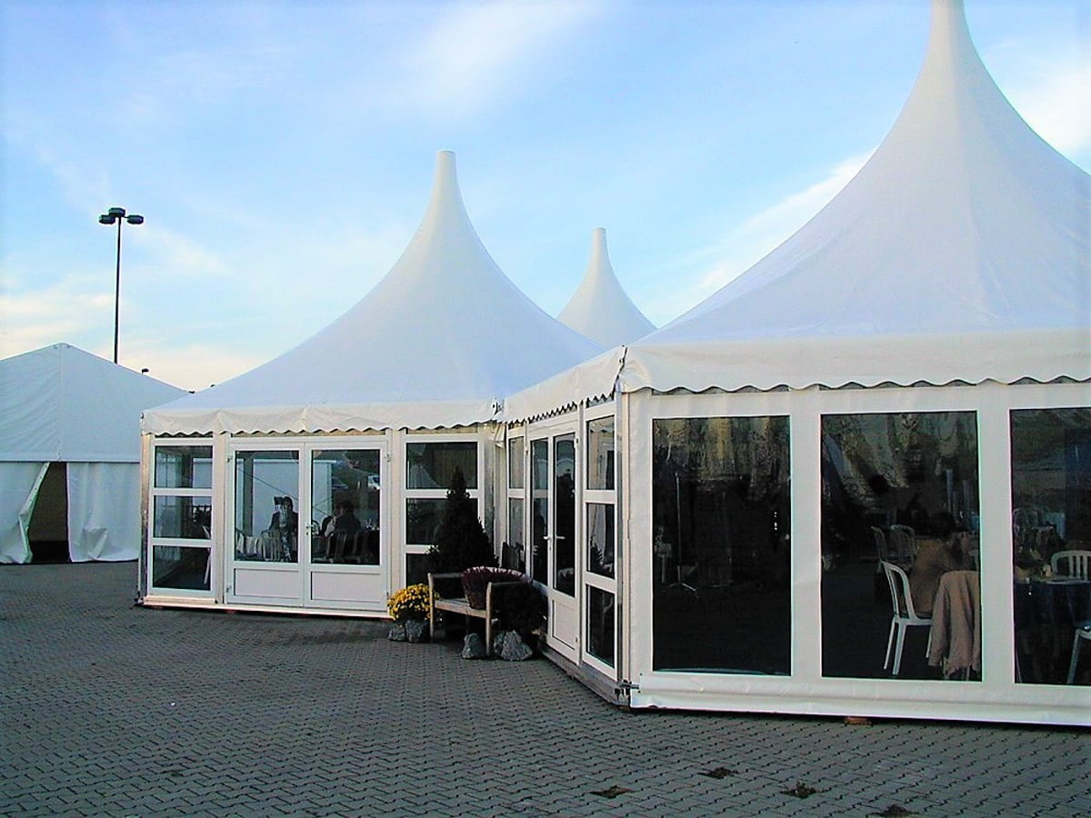 A HÖCKER P Series high peak roof multi sided marquee being used at a function