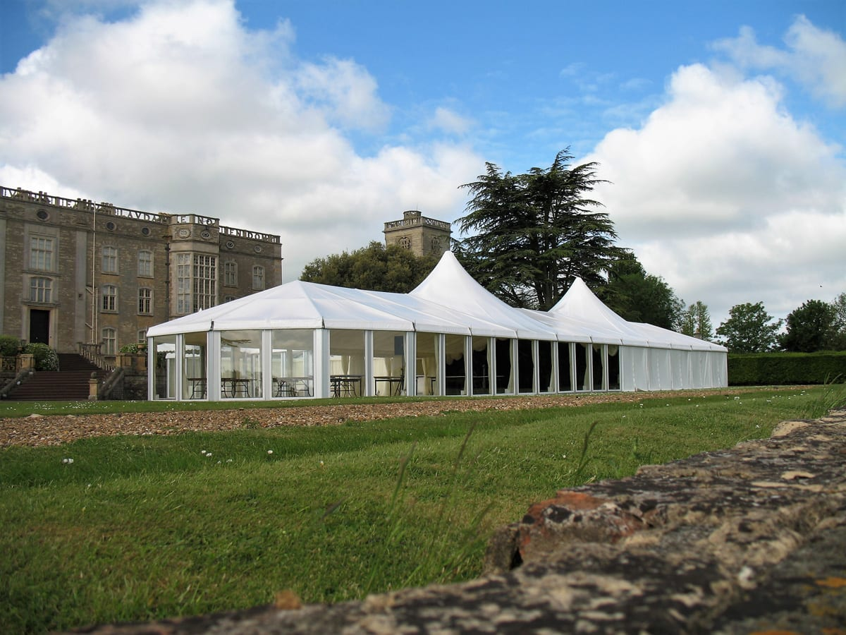 A HÖCKER P Series high peak roof event marquee being used for a function next to a castle