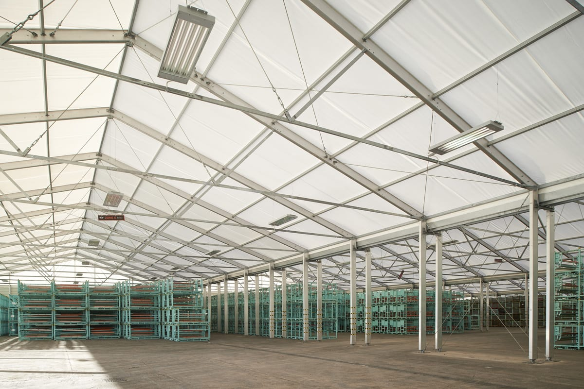 Inside an industrial canopy building with shelving units for storage