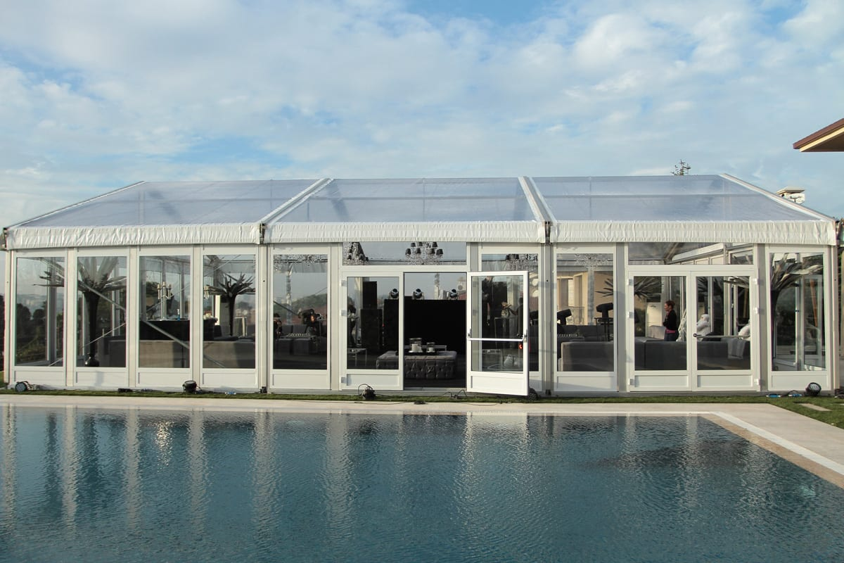 A HTS tentiQ GZ premium large event tent used as a lounge area next to a swimming pool