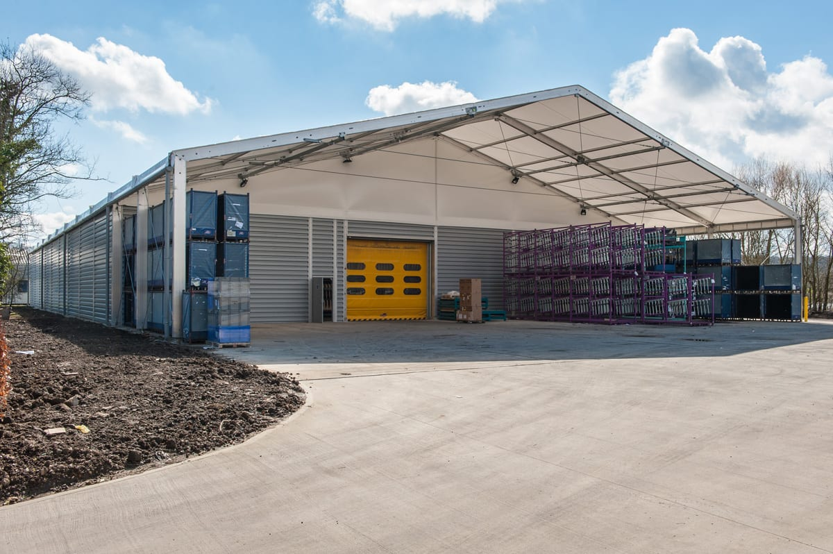 A Large industrial warehouse with a front canopy and roller shutter doors