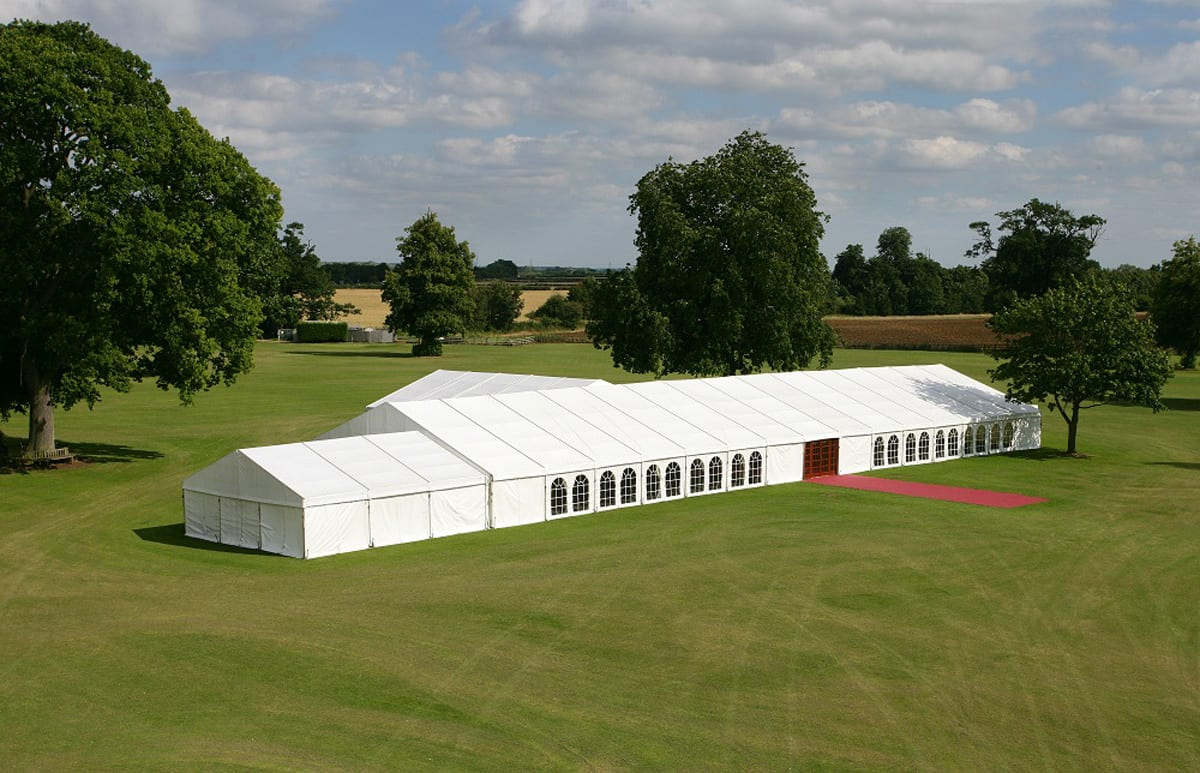 A RÖDER HTS (PZ) A-frame tent with red carpet at entrance being used at a party