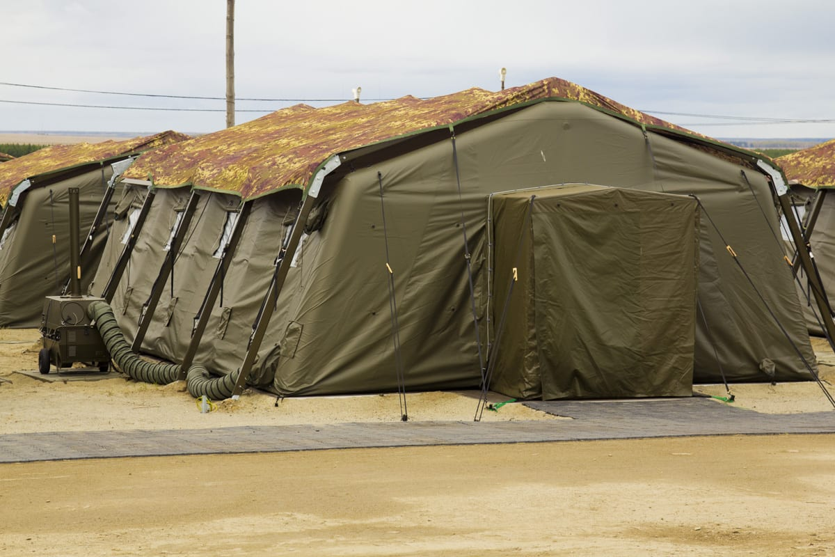 Military accommodation tent with a camouflage roofing